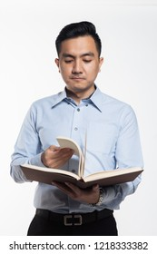 Asian man reading book looking for answer