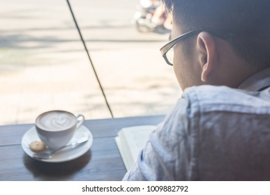Asian man reading books and drinking coffee