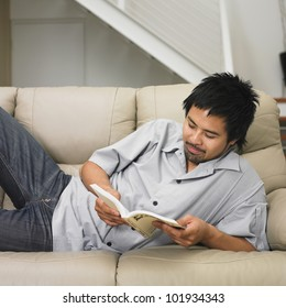 Asian man reading on sofa