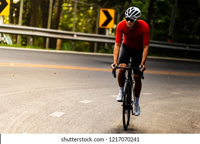 Asian man in red cycling jersey riding on road bike with willful face.