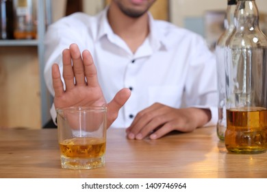 Asian man refuses to drink a alcohol by stopping hand sign. Male alcoholism concept. Treatment of alcohol addiction. Quit booze and alcoholism