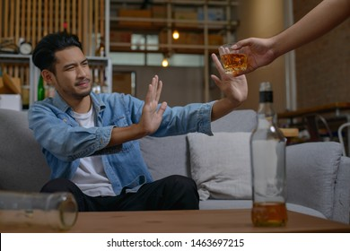 Asian man refusing alcohol from friend or another person because he want to quit drinking or will drive a vehicle.