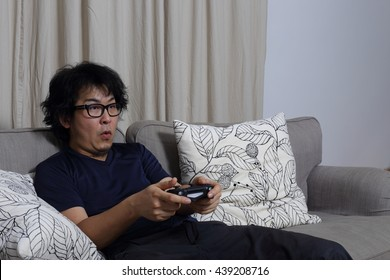 The Asian man relaxing in living room.