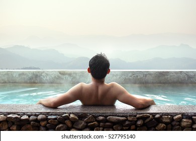 Asian man relaxing in outdoor hot bath with mountains view.