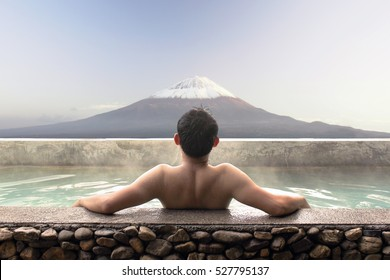 Asian man relaxing in outdoor Japanese bath with Mt. Fuji view.