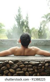 Asian man relaxing in outdoor japanese hot bath.