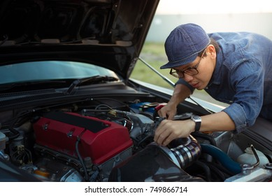 Asian man is repairing and tuning modified super car at engine bay seriously.