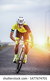 asian man riding bicycle on asphalt road against sunrise