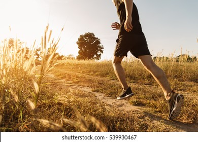 Asian Man running on a rural road during sunset