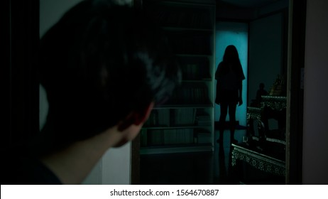 An asian man saw Thai lady ghost across the room stared at him. the lady ghost is completely in silhouette.
