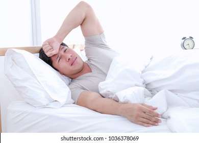 Asian man shocked while he look at the alam clock and see that he wakes up late for an appointment. Handsome fitness guy waking up late for trainning.
