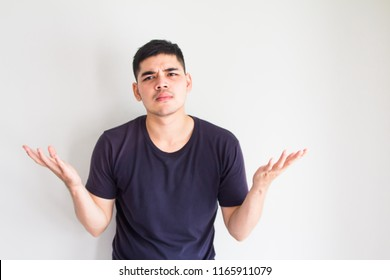 Asian man showing I don't know gesture,arms out asking why what's the problem who cares.Negative human emotion facial expression feelings