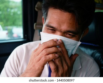 asian man sick and wearing protective mask to prevent sneezing from allergy.