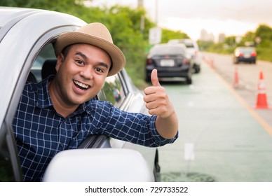 Asian man sit in car and showing thumb up