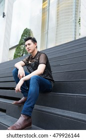Asian man sits and thinks, at outdoor.