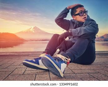 Asian man sitting by Lake Kawaguchiko and enjoying the beautiful view of Mountain Fuji in the morning