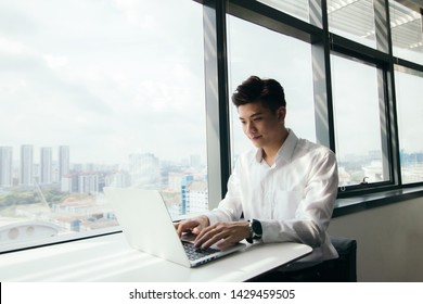 Asian Man sitting by the window desk using his laptop doing work