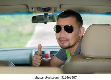Asian man sitting in car and doing thumb up and looking back