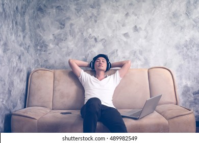 Asian man sitting on sofa at home,listening a music with laptop.