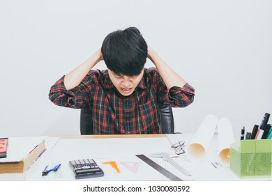 Asian man sitting stress with work on the table and sunset background