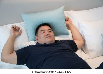 Asian man sleeping comfortably in bed / fat man with relaxing.