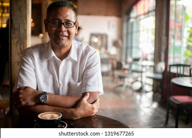 Asian man smiling.Small business owner relaxing in vintage cafe,drinking coffee. - Image