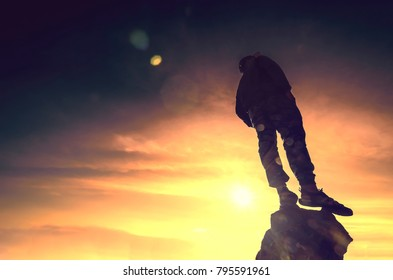Asian man stand extend the arms on the rocks in at sunset sky.
