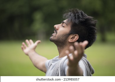 Asian man standing with arms raised outdoors. Concept about freedom, faith and celebration.