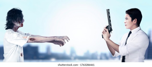 Asian man standing with a gun on his hand ready to attack zombies on the city