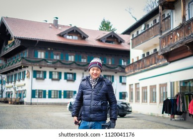 Asian man standing on main street in Oberammergau with beautiful view of old town city and building paintings in background, Oberammergau, Germany