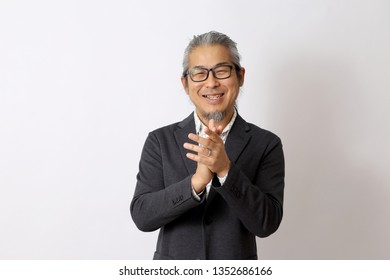 The Asian man standing on the white background.
