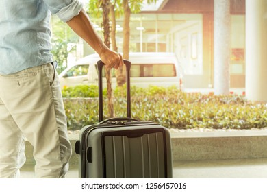 Asian man standing with suitcase luggage in the airport terminal travel concept.