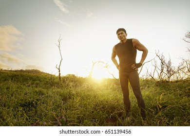 Asian man standing in tall grass