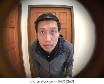 Asian man standing and waiting in front of door See-through the peephole of door for security in hotel