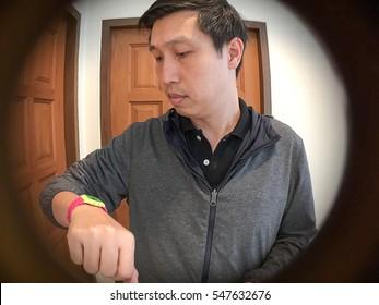 Asian Man Standing And Waiting In Front Of Door See Through The Peephole Of  Door