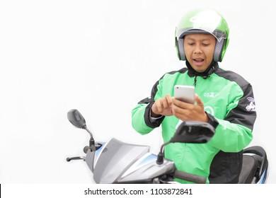 asian man surprised using smartphone on motorcycle with green jacket gojek. Yogyakarta Indonesia. june 03, 2018