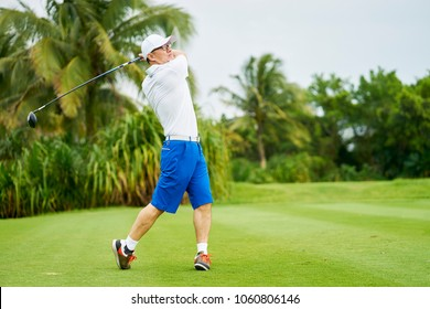 Asian man swinging club in golf course in summer