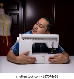 asian man tailor hug electric sewing machine be passion and love in occupation