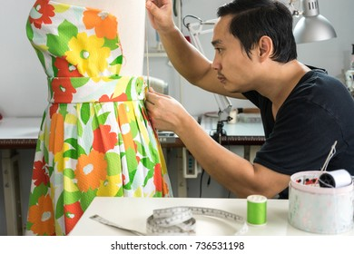 Asian man tailor used measurement tape dress on dummy