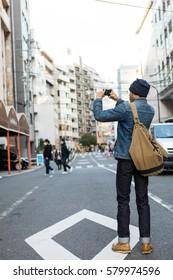 Asian man take photo with smartphone, Tokyo, Japan.