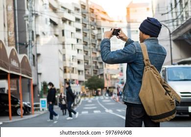 Asian man take a photo with smartphone on street, Shibuya, Tokyo, Japan.