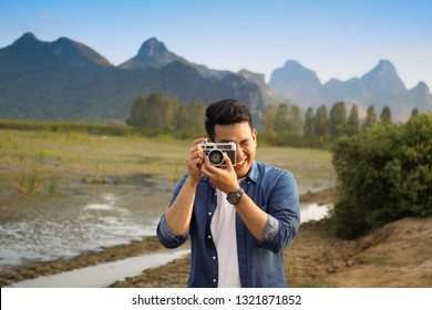 Asian man take photo with vintage camera in mauntain view