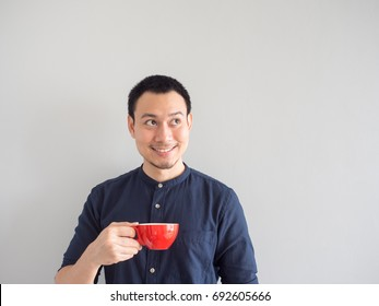 Asian man take a sip of coffee in red cup.