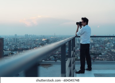 Asian man taking cityscape photo on building rooftop in low light situation. Photography, office people, or hobby concept. With copy space