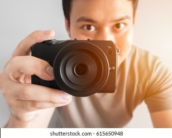 Asian man is taking photo of you with small mirrorless camera.