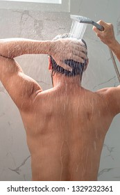 Asian man taking a shower in the bathroom.