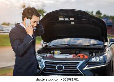 Asian Man talking on a cell phone by a broken car