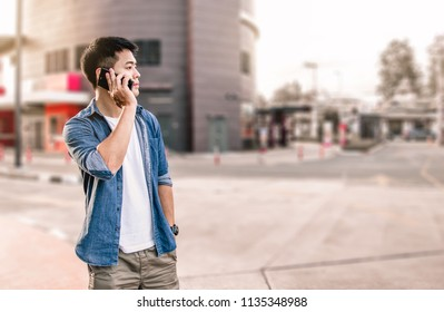 Asian man talking on mobile phone outdoor, A man using smart phone on the corner of road, Portrait asian man calling on mobile phone on street, A man wear denim shirt using smart phone outside