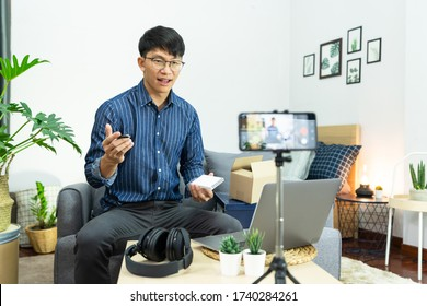 Asian man technology blogger or Social media influencer presenting and review on product by smartphone or camera on tripod recording live video for his channel on foreground creator vlogger filming