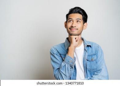 Asiatischer Mann denkt und lächelt.